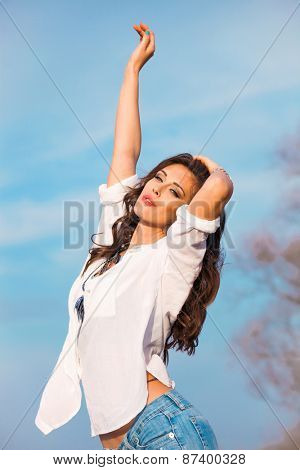 young beautiful woman in white shirt and blue jeans enjoy in sunny day, blue sky in background