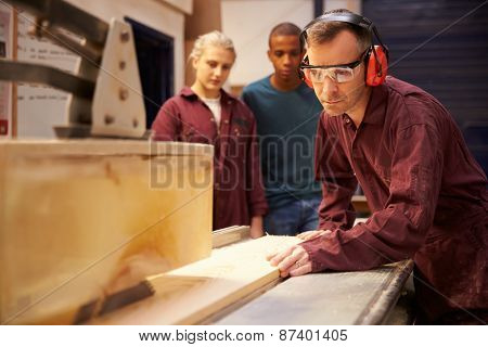 Carpenter With Apprentices Using Circular Saw In Workshop