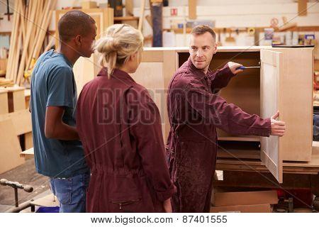 Carpenter With Apprentices Building Furniture In Workshop