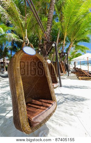 Empty Hanging Wicker Chair On Tropical Beach