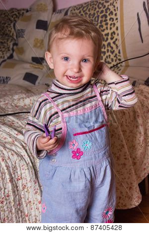 Cute blonde baby girl with beautiful blue eyes stands and smiling