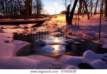 A frozen scenic small river on winter evening at blue hour time