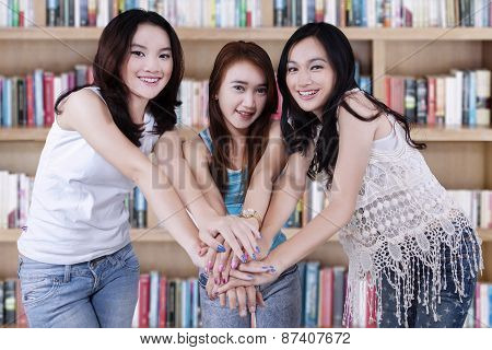 Three Student Joining Hands In Library