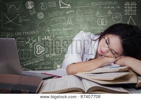 Tired Teenage Student Sleeping On Desk