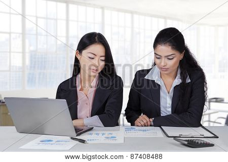 Two Employees With Paperwork In Office