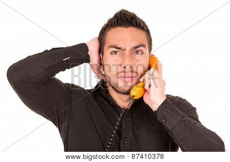 closeup portrait of handsome hispanic man talking on corded retro phone