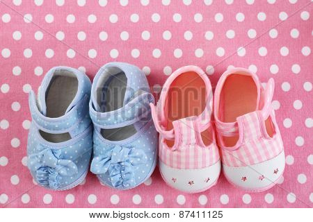 Baby shoes on cloth background