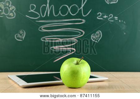 Digital tablet and apple on  desk in front of blackboard