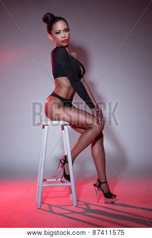 Sexy Young Woman Wearing Black Leotard Sitting on a Stool While Looking at the Camera. Captured in Studio with Gray Background.