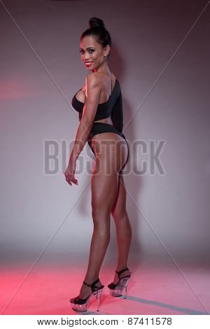 Full Length Shot of a Smiling Young Bodybuilder Woman Standing in Black Leotard and High Heels Against the Gray Wall.
