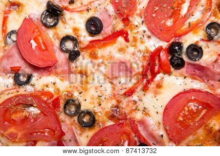 Texture of tasty Italian pizza with ham, tomatoes and olives, top view