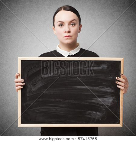 Retro portrait of a strict young woman holding a blackboard