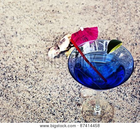 Beach background with copys pace, beach sand summer theme, cocktail glass with umbrella and a straw