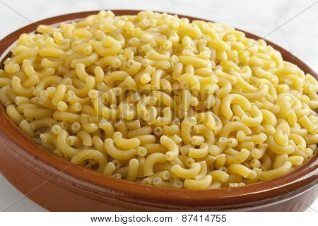 Traditional Italian macaroni in a brown dish close up