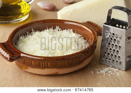 Bowl with grated Italian pecorino romano cheese, olive oil and garlic