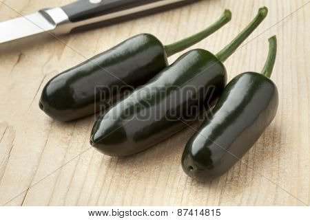 Three fresh green Jalapeno chili peppers on a cutting board