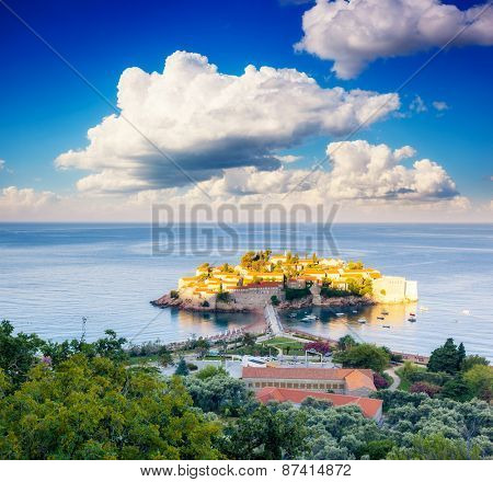 Fantastic view of the Sveti Stefan, small islet and resort in Montenegro. Dramatic morning scene. White fluffy clouds. Balkans, Adriatic sea, Europe. Beauty world.
