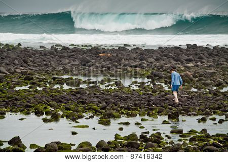Unidentified tourist walking along the rocky coastline in a scenic beach of San Cristobal Island, Ga