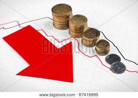 Coins and red arrow on graph document close up