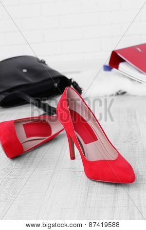 Female shoes and briefcase on floor background
