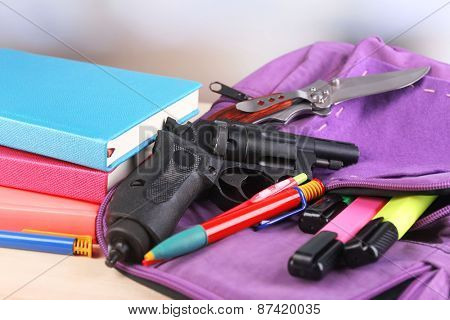 Gun in school backpack on wooden table, on bright background