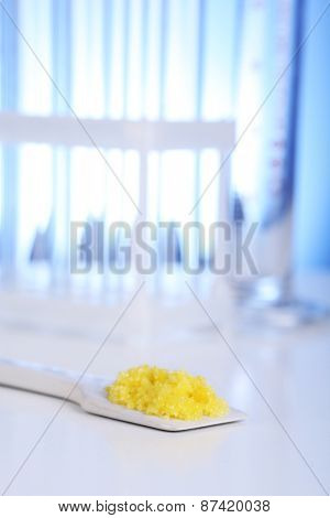 Laboratory spatula with granules on blue background