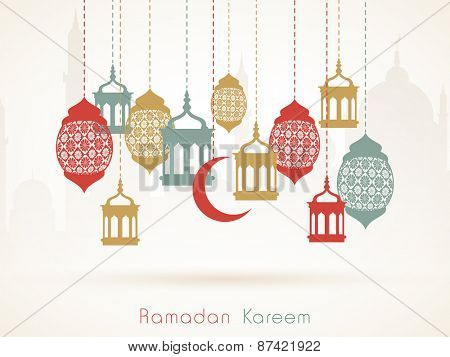 Hanging colorful arabic lamps or moon on islamic mosque silhouette background for holy month of muslim community, Ramadan Kareem celebration.