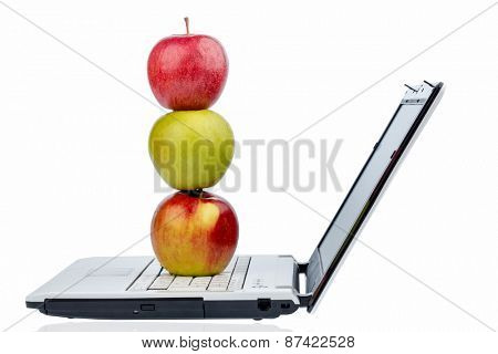 an apple is on the keyboard of a computer. symbolic photo for healthy and vitamin-packed snack.