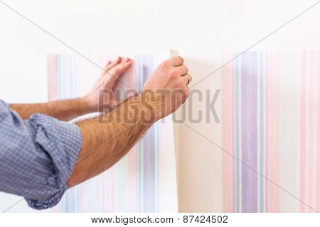 Handyman putting up wallpaper on the white walls