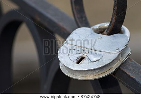 Old Silvery Padlock On An Iron Fence
