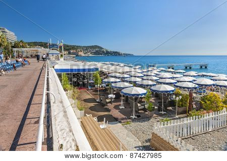 NICE, FRANCE - OCTOBER 2, 2014: English promenade or Promenade des Anglais runs along the city beach with restaurants, chairs and umbrellas.