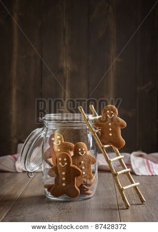 Gingerbread man on rustic ladder climbing into cookie jar