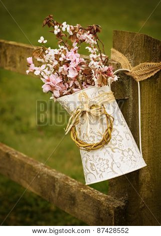 Spring blossom in jug hanging on rustic country fence
