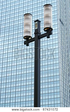 Street lamp against the facade of a modern skyscraper