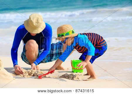 father and son building sand castle on the beach