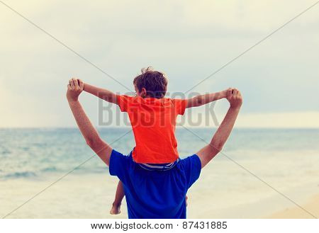 happy father and son playing on summer sea