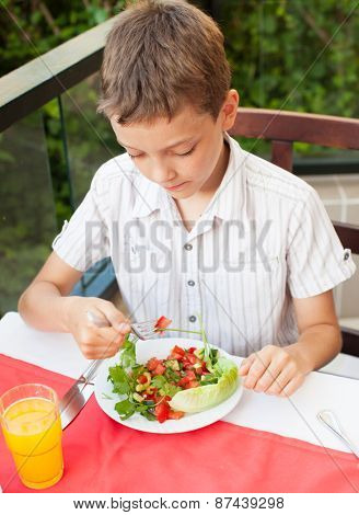 Boy eating salad at a cafe. Teenager eating outdoors