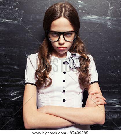 Sad Girl near blackboard. Child at school. Student at classroom