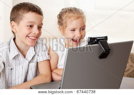 Ã?hildren communicate with online. Happy kids with laptop at home