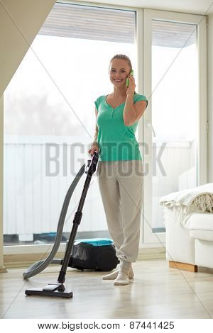 people, housework and housekeeping concept - happy woman with vacuum cleaner calling on smartphone at home