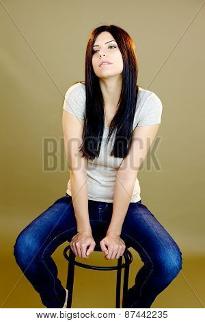 Beautiful Female Model Posing Sitting On Chair In Studio