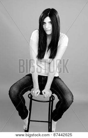 Black And White Portrait Of Beautiful Woman Sitting In Studio Smiling Looking Camera
