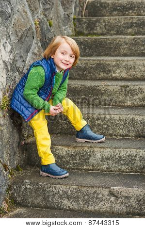 Fashion portrait of a cute little  blond boy, wearing colorful clothes