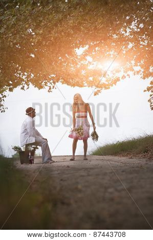 Happy attractive couple outdoors on dirt road under avenue of trees