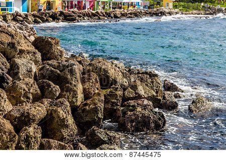Rock Seawall By Colorful Buildings