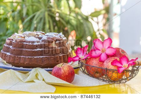 freshly baked home-made banana apple cake on natural background with fresh apples and flowers