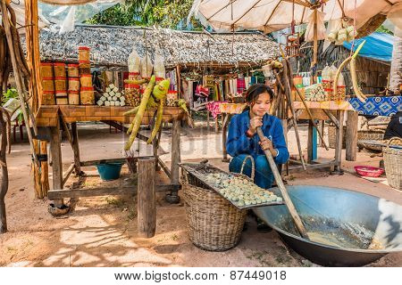 Angkor, Cambodia - January 2, 2014: girl making and selling sugar cane sweets at Angkor Cambodia on january 2nd, 2014