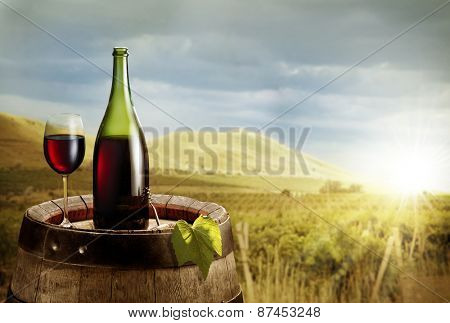 Still-life with glass of wine and bottle on the barrel in the vineyard.