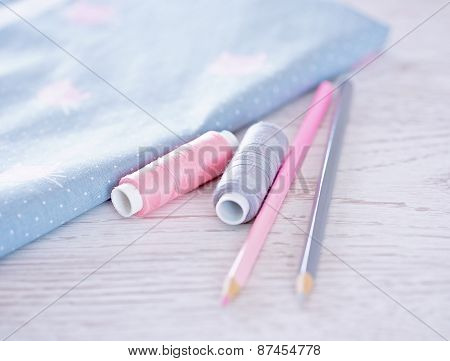 Sewing Materials, Pencils, Fabric On A Blue And Pink Color