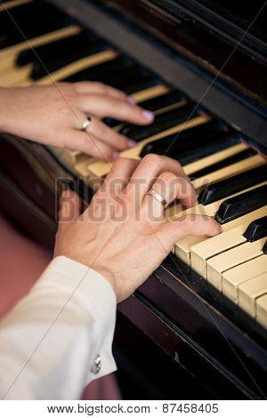 Toned Photo Of Newly Married Couple Playing On Piano